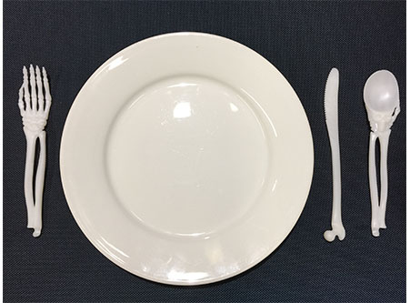 place setting of bone-style spoon, fork, knife around plate