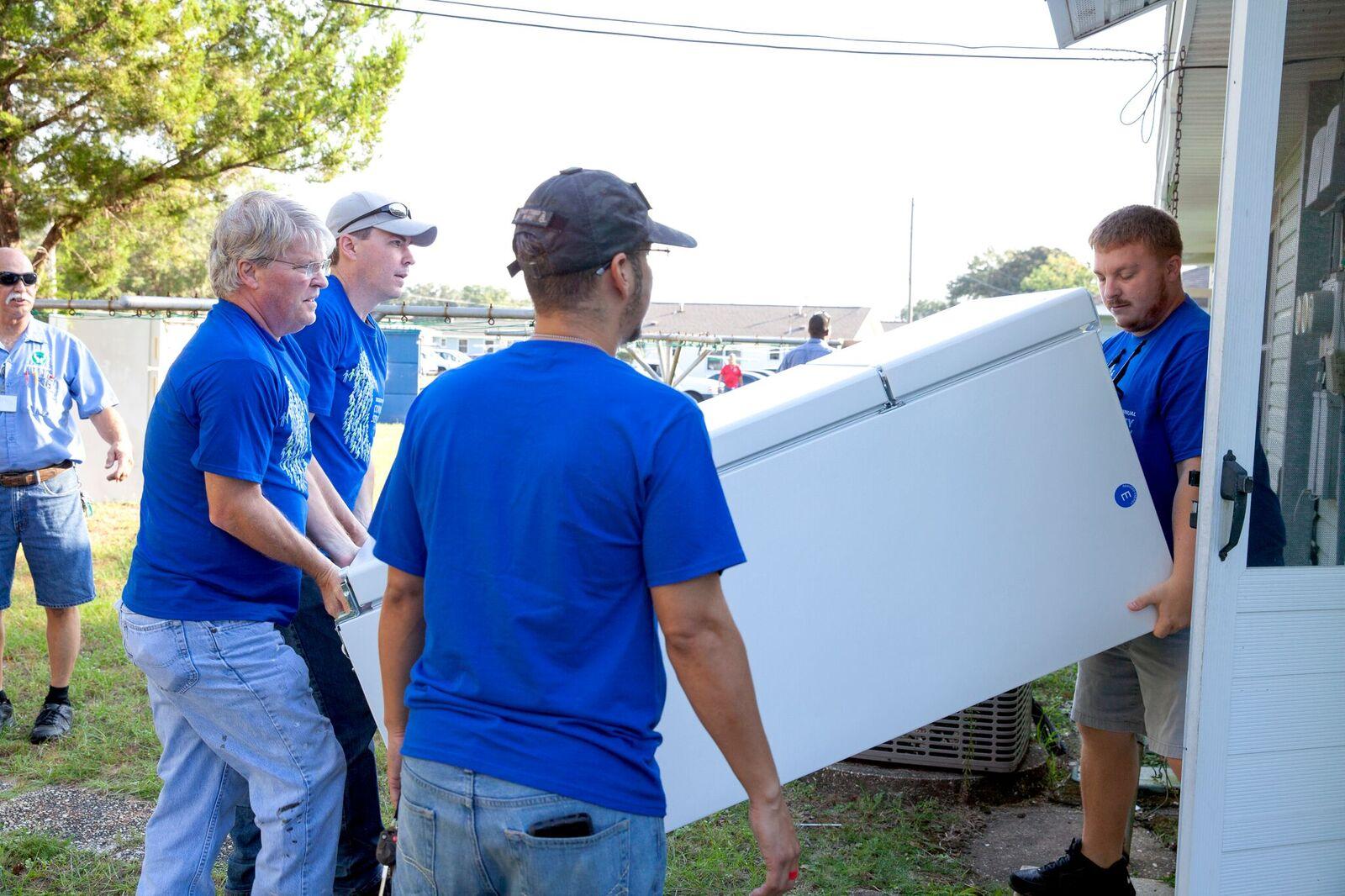 Securadyne volunteers carrying refrigerators into apartments at Moreno Court