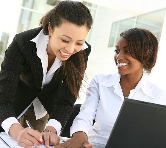 Two women laughing whie working together