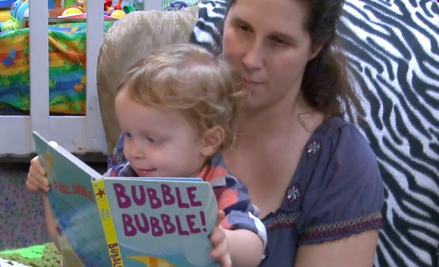 Woman reading the book Bubble Bubble to toddler