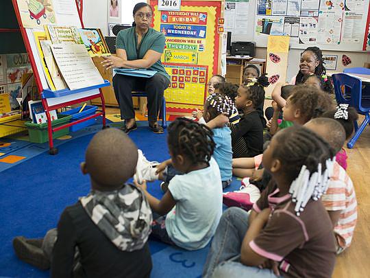 Children in class listening to a teacher