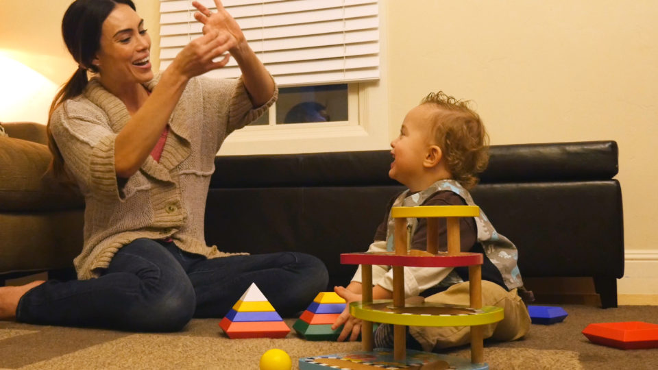 Image of a woman playing with child while sitting on the floor of a living room