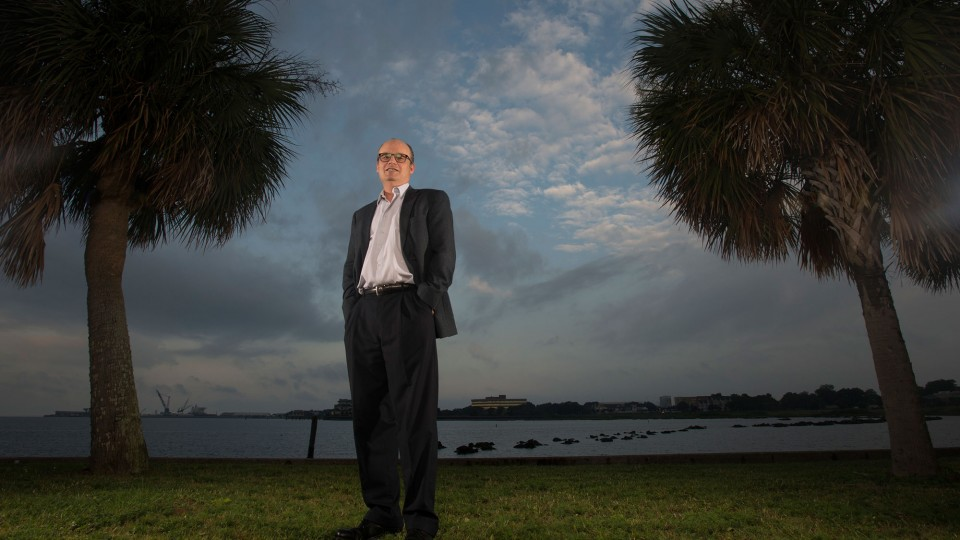 Man standing by the bay in between two palm trees