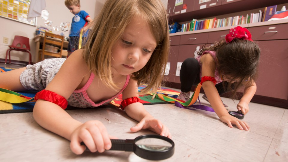Claire Hedgepeth uses a magnifying glass to investigate along with others in a pre-K class at Myrtle Grove Baptist Church Pre-School Learning Center