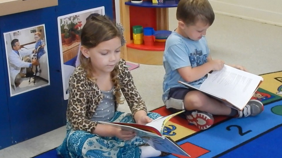 Two children reading books in a classroom