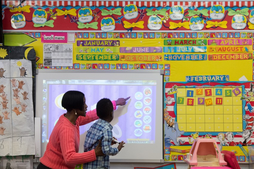 Myra Ewing helps Asy McCray use a Mimio Board at T.R. Jackson Pre-K center in Milton. Photo credit: Michael Spooneybarger.