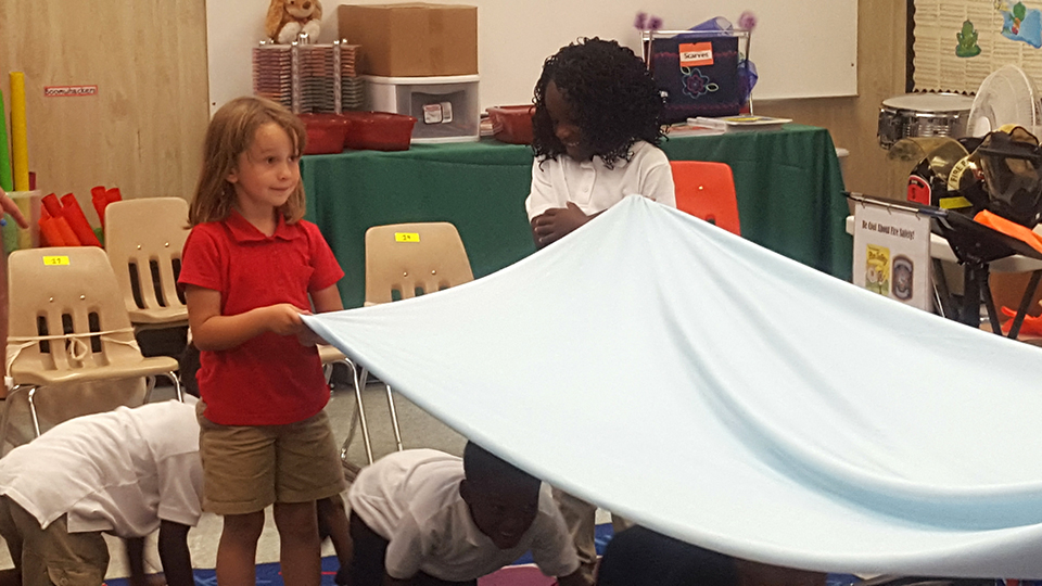 Children in a classroom building a tent