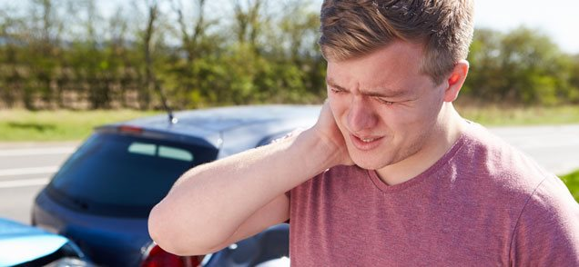 image of man rubbing neck standing in front of car crash