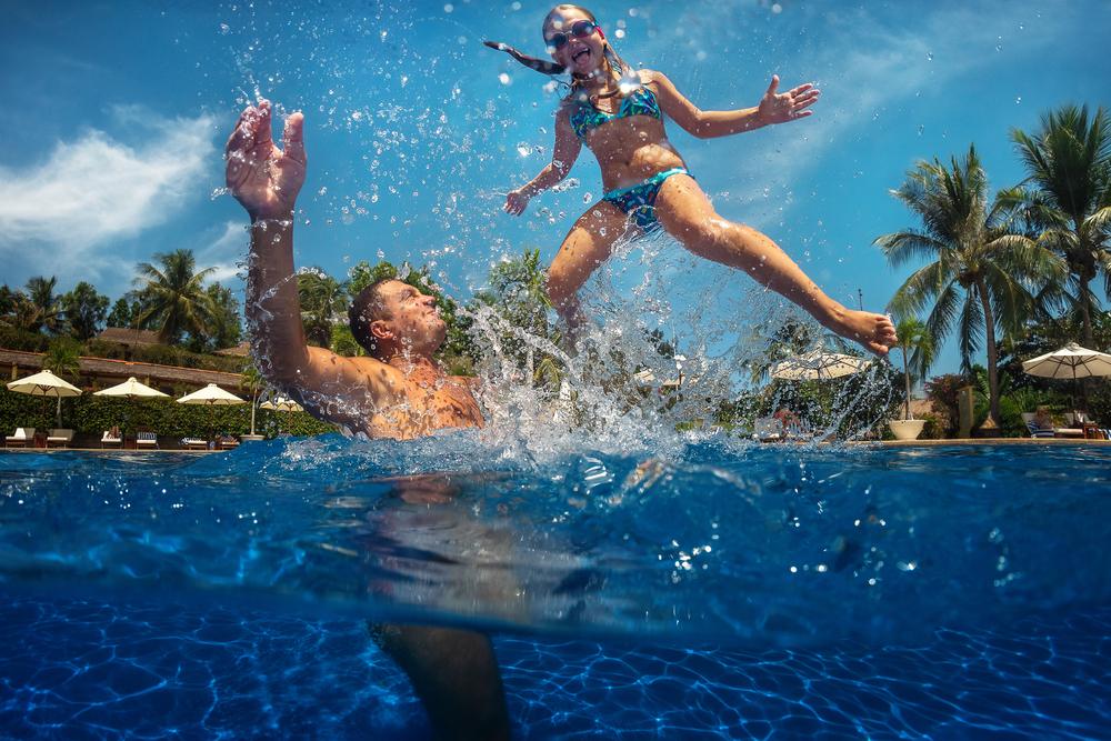 Father & Daughter splashing in pool