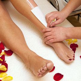 woman having waxing and nail service