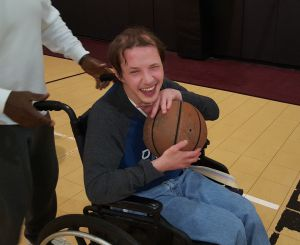 person in a wheelchair and holding a basketball