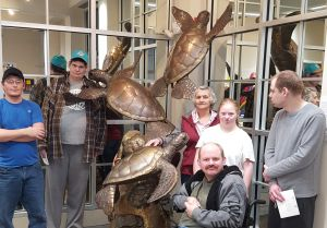 a group of people with a sea turtle statue