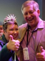 man and woman with a tiara smiling while holding a thumbs up
