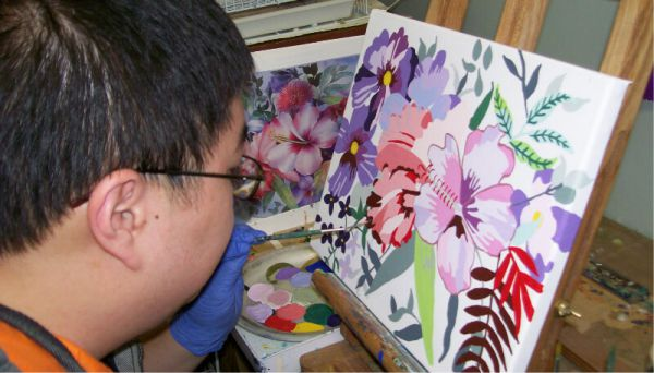 Boy painting flowers on a canvas