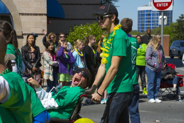 Man pushing a man in a wheelchair in a parade.