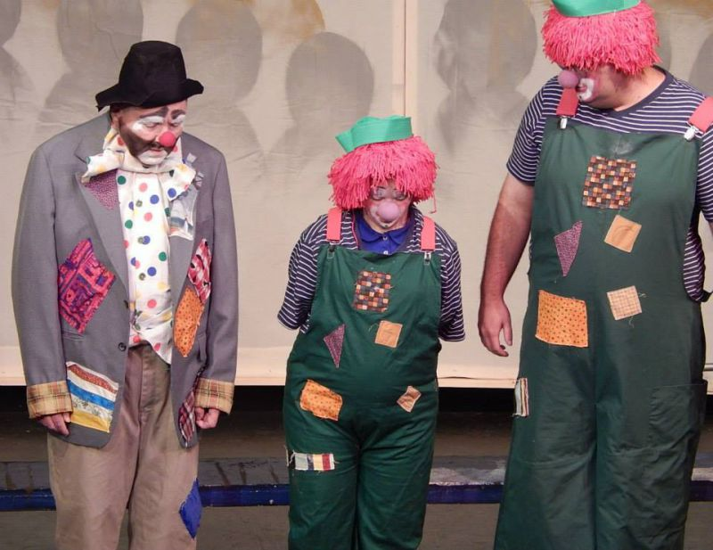 image of three people performing on stage as clowns