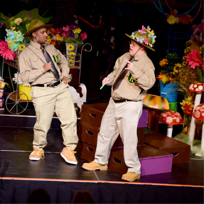 two males in ranger costumes with flowers in their hat