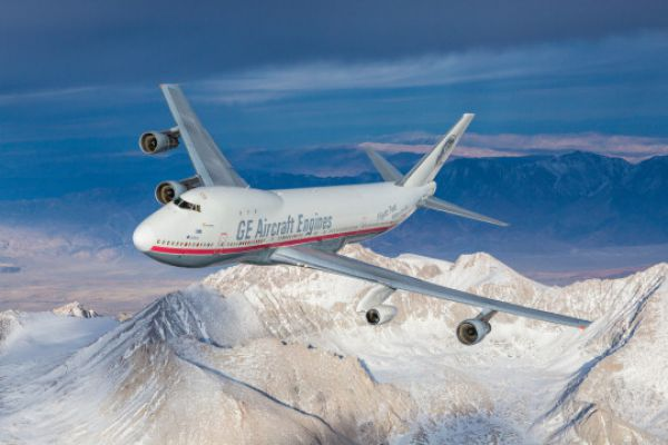 GE jet flying over mountains