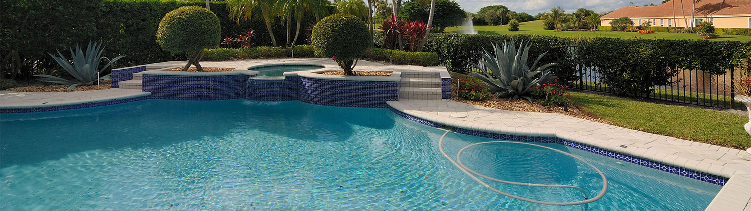 Beautiful two level pool with a waterfall from the top level jacuzzi tub into the lower level pool with scenic palm trees and aloe plants in the yard surrounding the pool