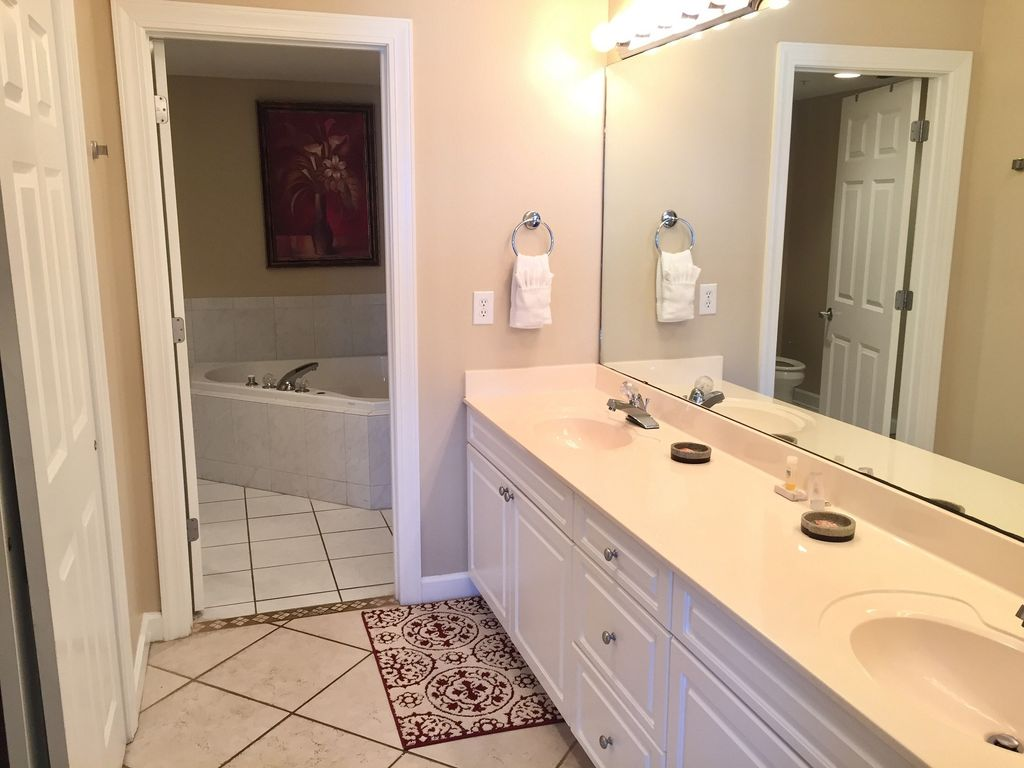 Master bath with double sinks, walkin closet, jacuzzi tub and glass shower