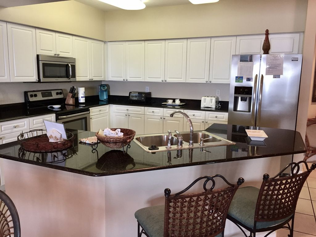 Fully stocked stainless kitchen with breakfast bar