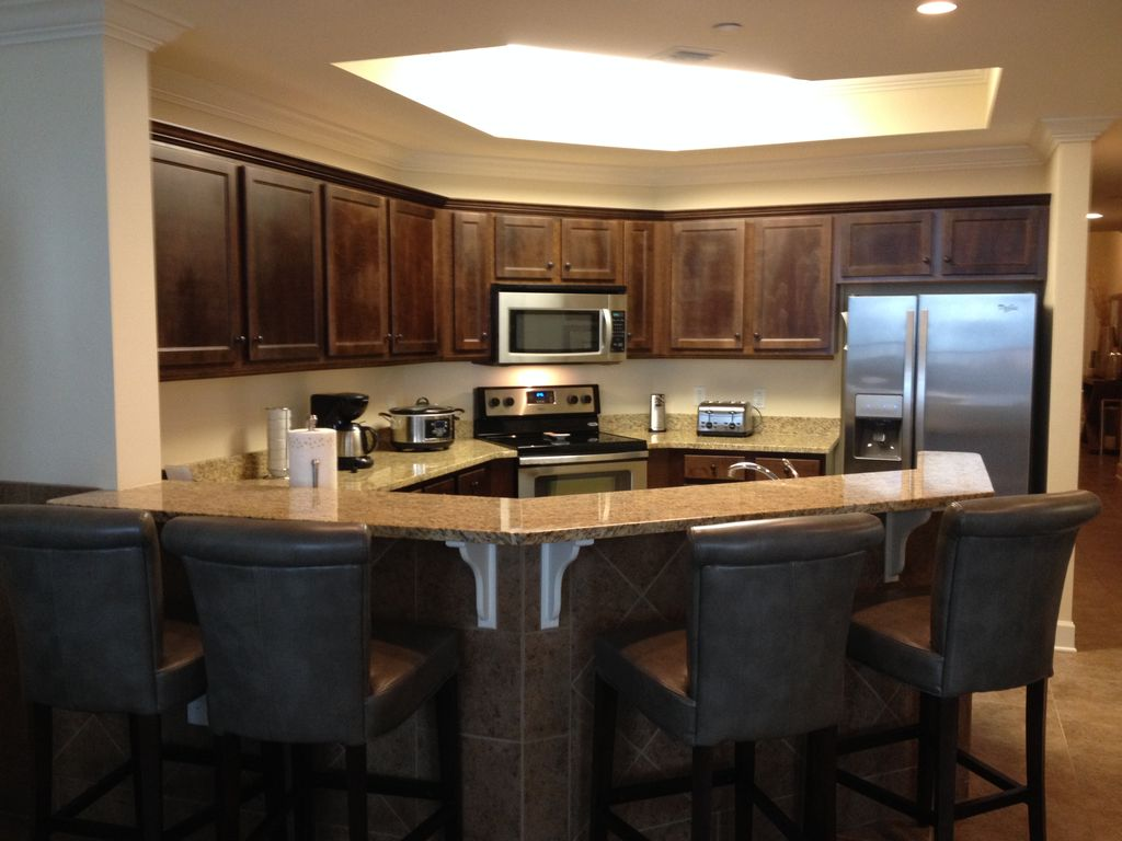 Kitchen with all stainless steel appliances and seating for 4