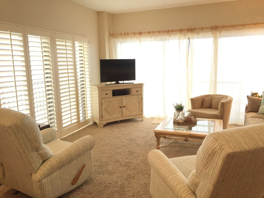Living room opening to beach front balcony with lagre HDTV and DVD