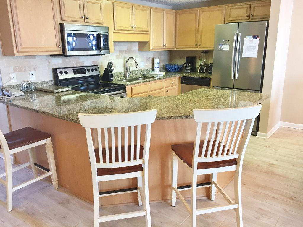 Spacious kitchen with granite counter top and breakfast bar with seating for three