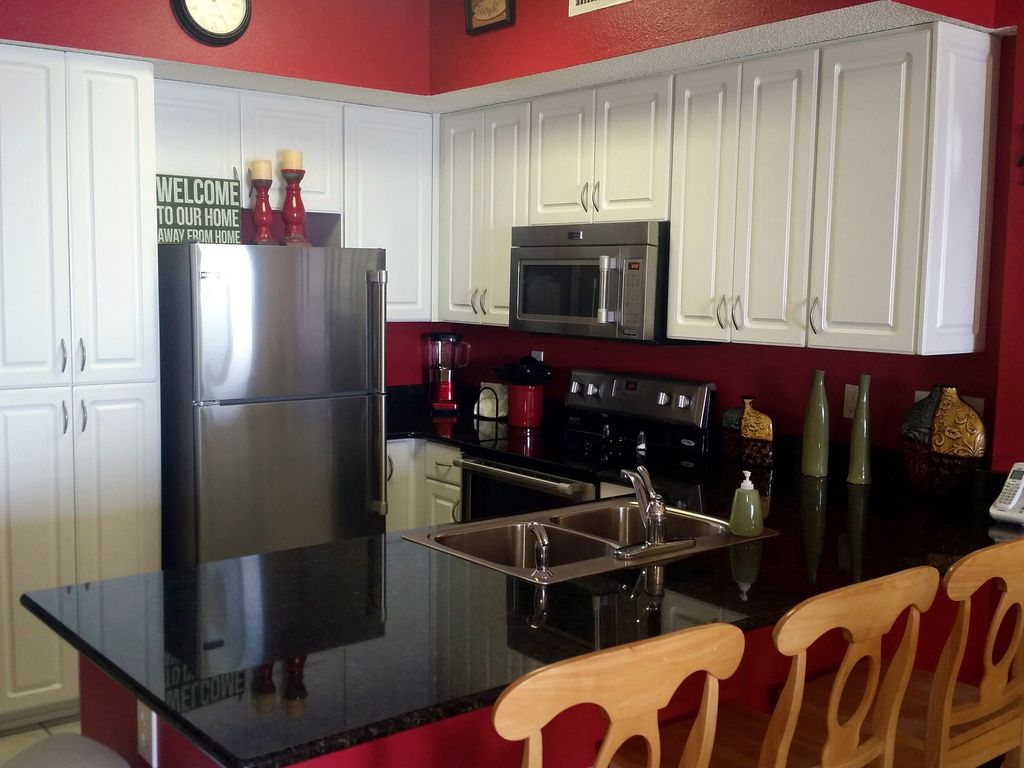 Kitchen with granite countertops and breakfast bar seating for three