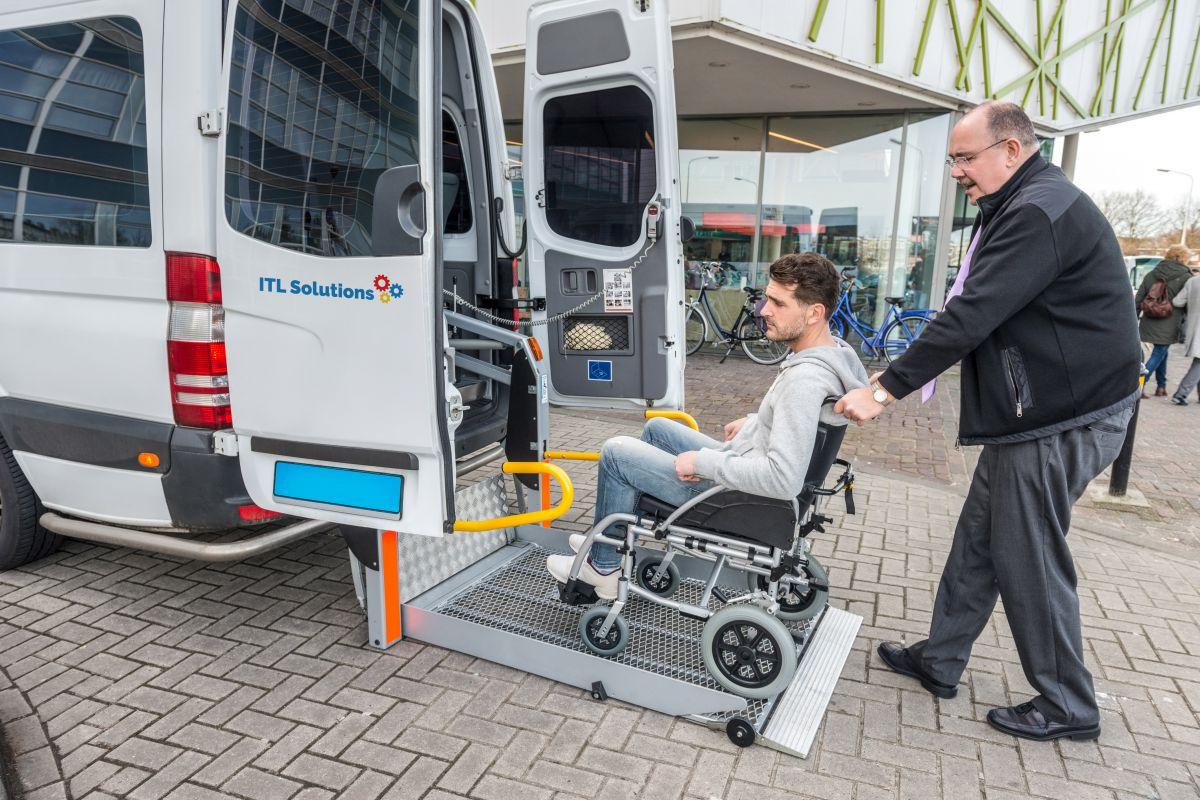 Man in wheelchair pointing at handicap sticker on bus