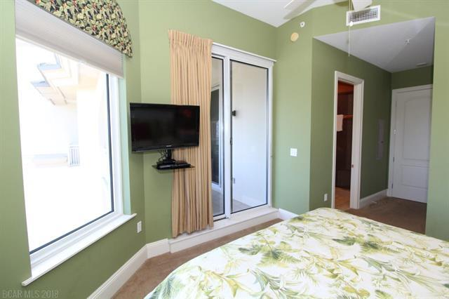 Bedroom with green floral comforter on the bed with large windows