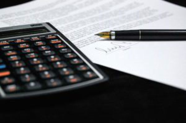 image of a calculator next to a paper and a pen