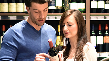 Man and woman comparing two bottles of wine inside wine market