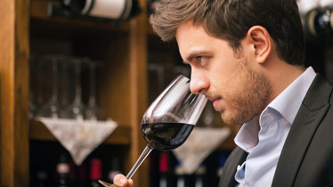 man sniffing red wine inside wine market
