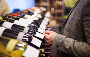 Line of wine bottles laying on a wine rack while man views label of a bottle of wine