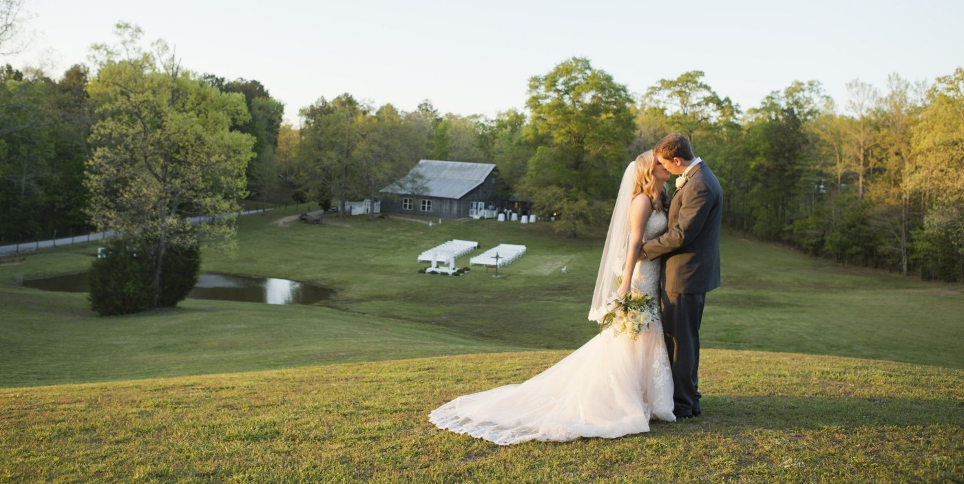 An Image of a bride and groom kissing on a hill