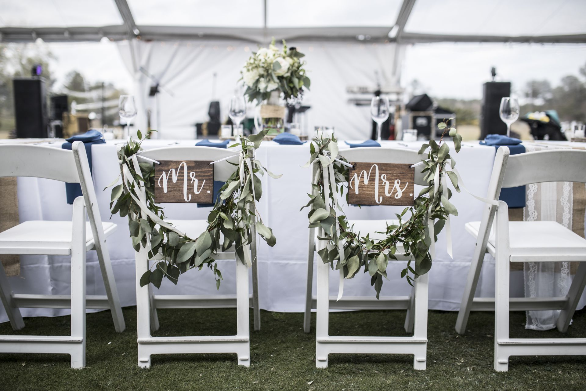 An image of a table at a reception with two decorated chairs