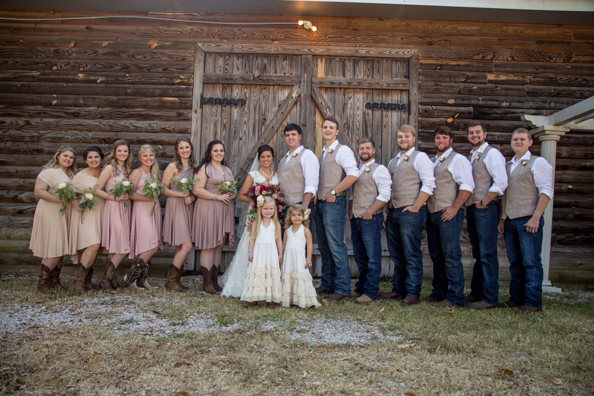 An image of a bridal party posing for a picture in front of a barn
