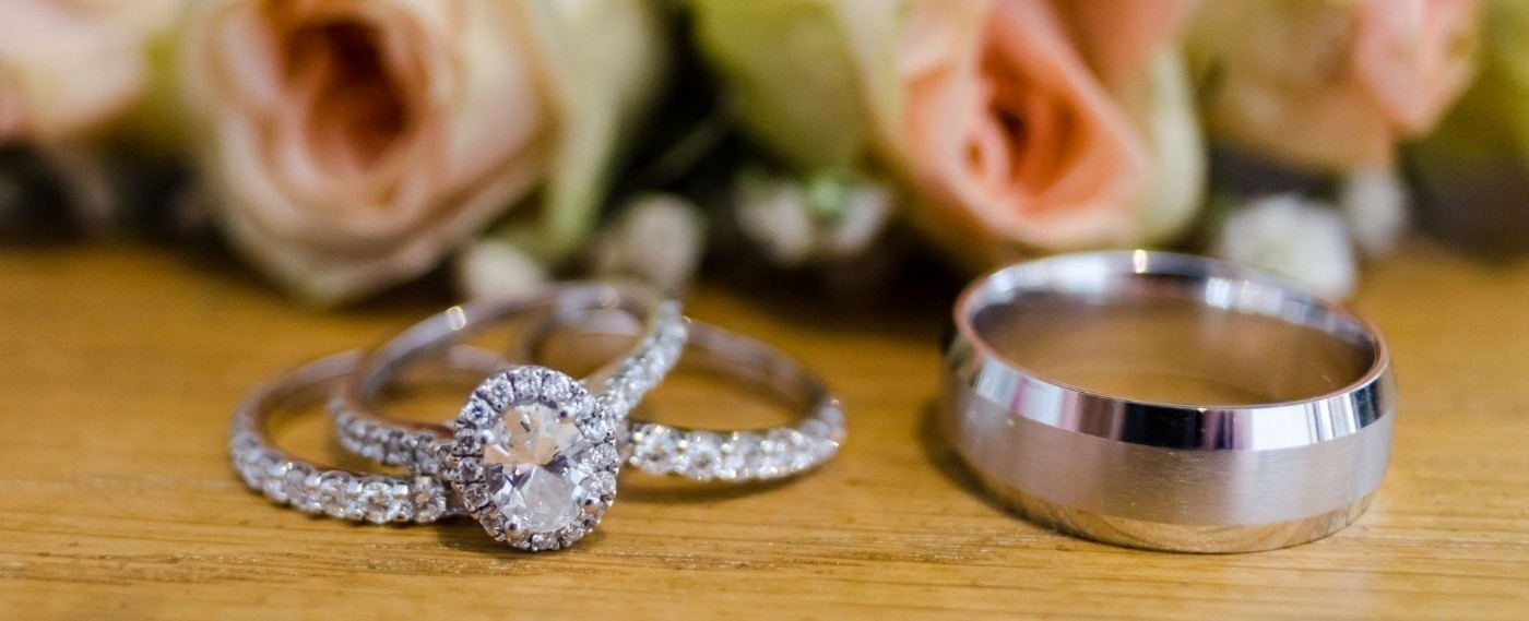 An Image of Brides engagement and wedding band and groom's wedding band siiting on a table
