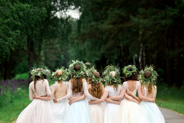 An image of bridesmaids from the back arm in arm