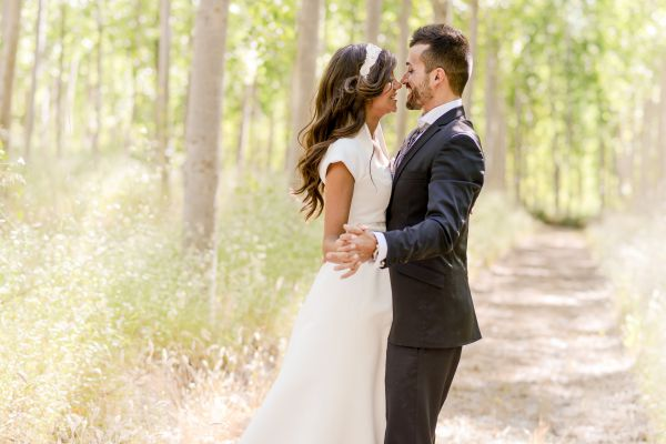 An image of a bride and groom kissing in field