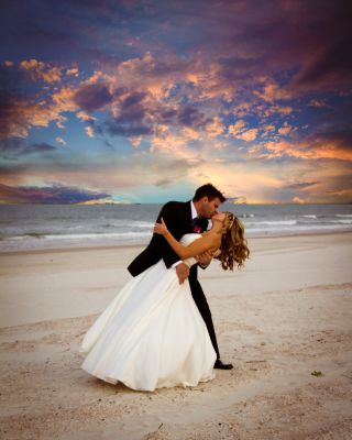 Groom dipping bride for a kiss on the beach