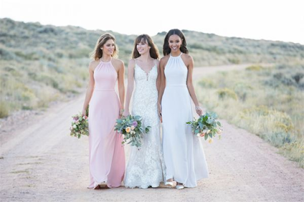 three women walking on a dirt road in bridesmaid dresses holding bouquet of flowers