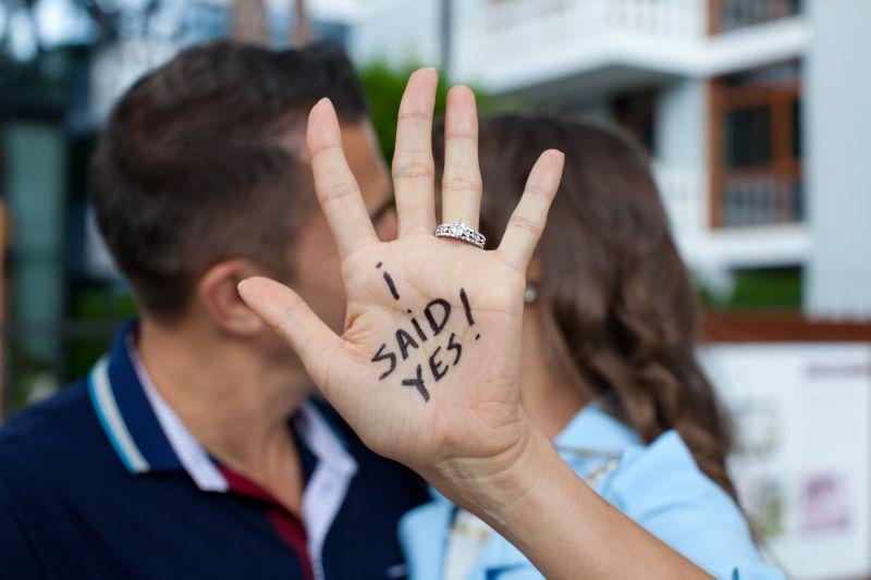 Man and woman kissing behind her hand with the words I said yes