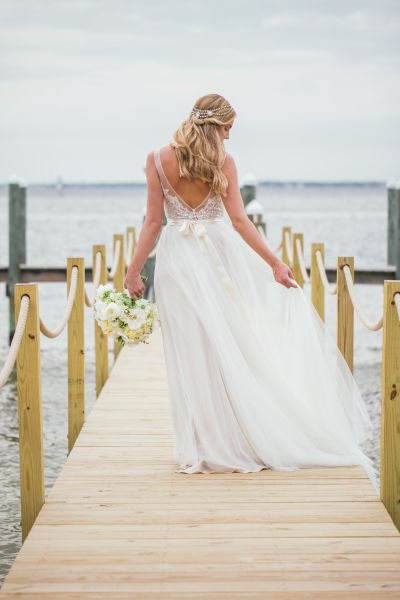 Bride walking on a pier with a bouquet of flowers in hand
