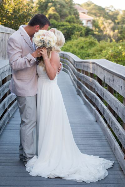 Bride and groom kissing behind a bouquet