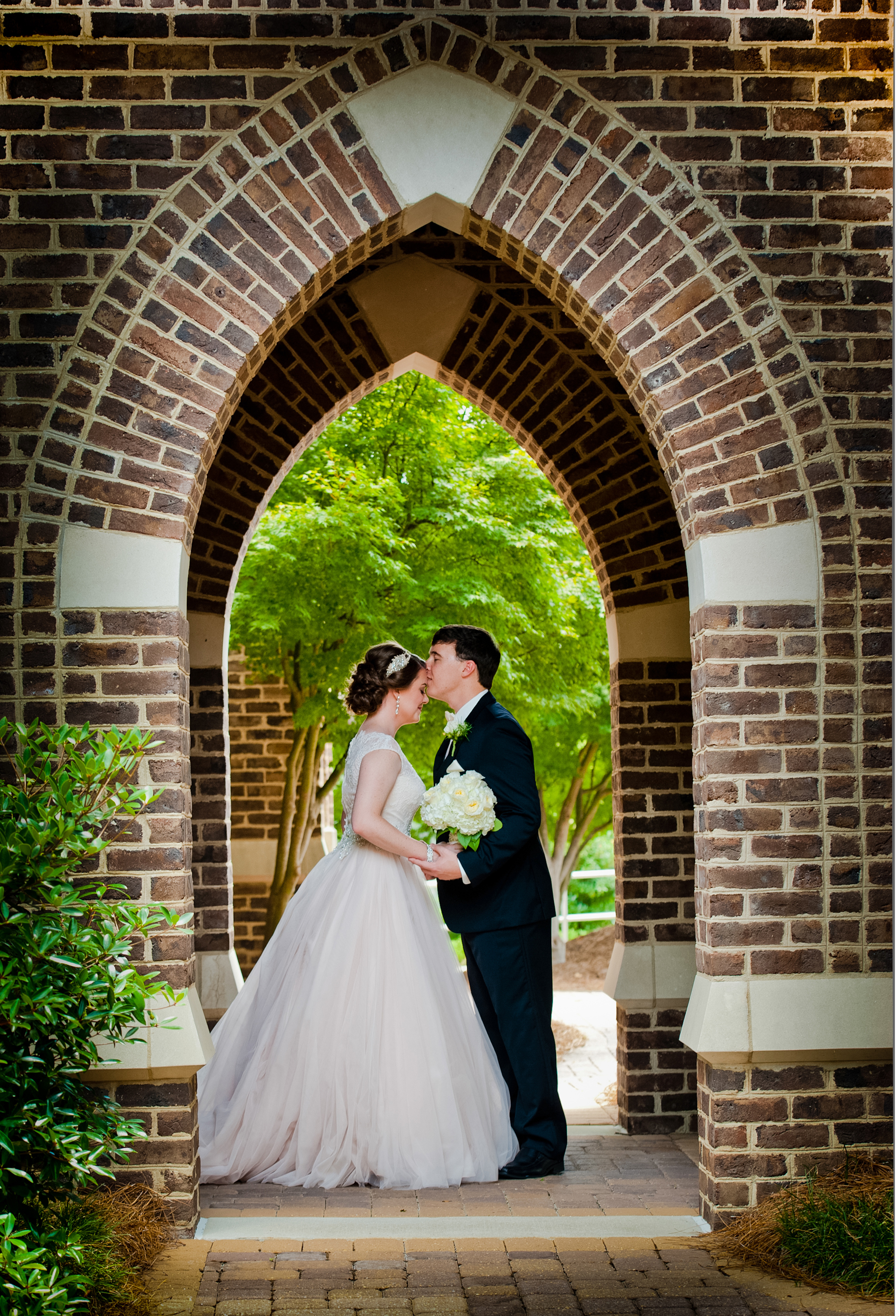 Bride and groom standing in an outdoor archway