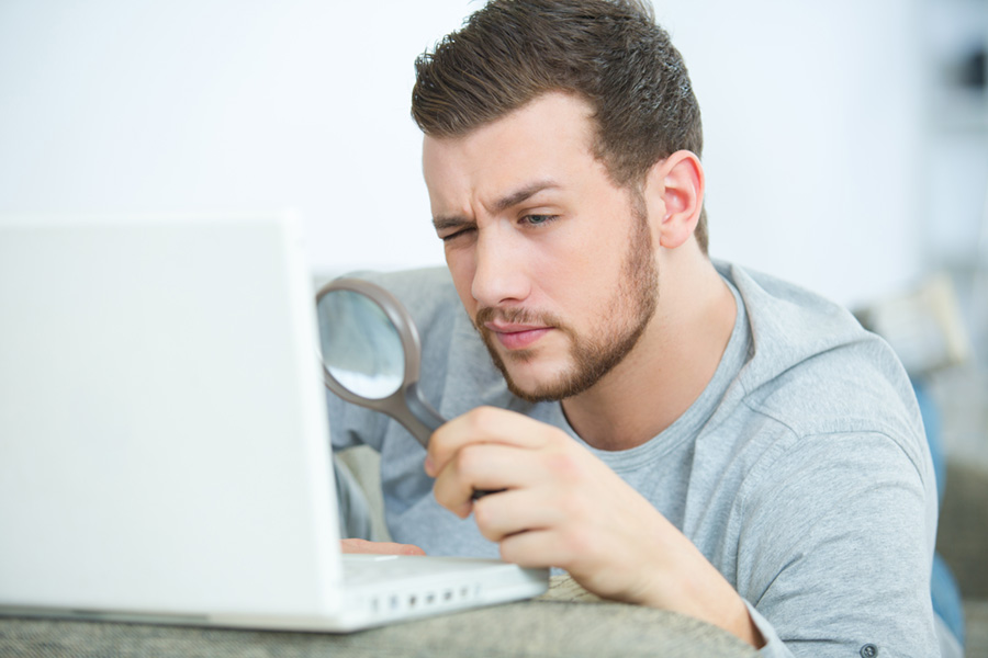 man using a magnifying glass to view laptop