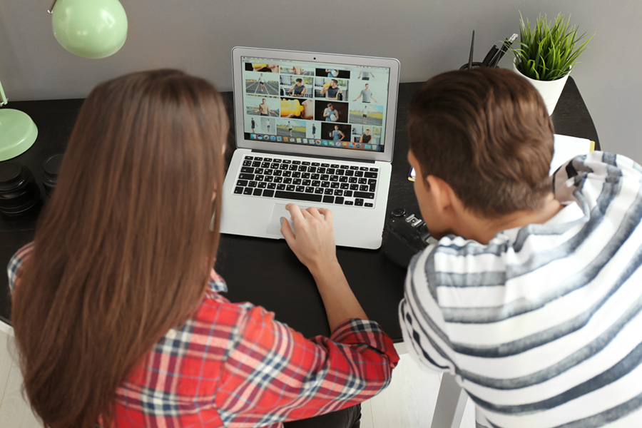 woman and man viewing a photo gallery on a laptop at a desk, the woman is on the right she has shoulder length hair, the main is on the left and has short hair