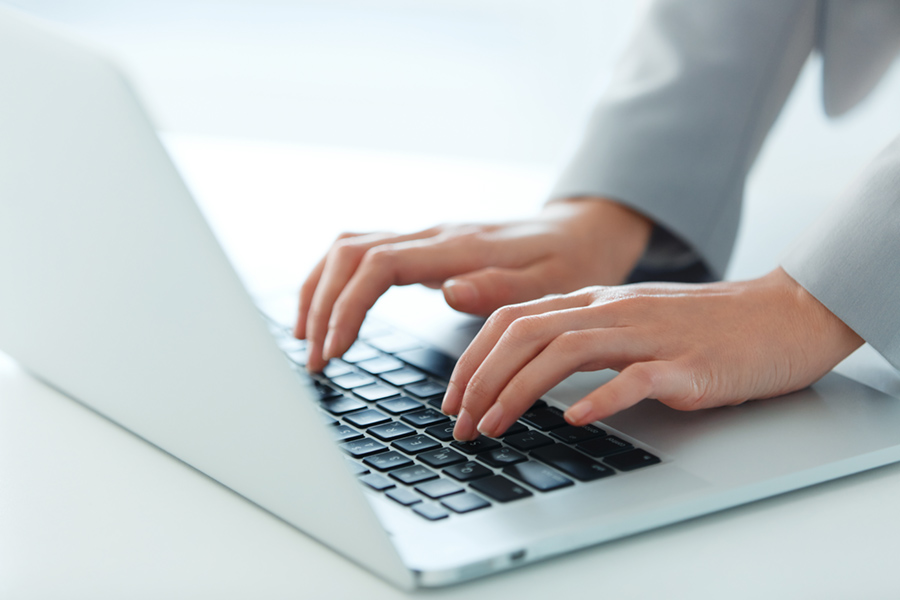 Image of womans hands on laptop keyboard